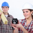 Carpenters and their piggy bank. — Stock Photo