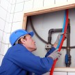 Stock Photo: Plumber tuning piping