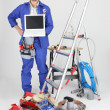 30 years old artisshowing laptop in room full of tools — Stock Photo #8107303