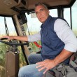 Farmer sitting in the cab of a combine harvester - Stock Photo