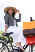 A woman at bike who did some shopping — Stock Photo