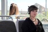 Ung kvinna lyssna på hennes hörlurar på en spårvagn — Stockfoto