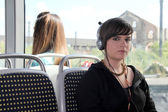 Junge frau, hören sie kopfhörer in der straßenbahn — Stockfoto