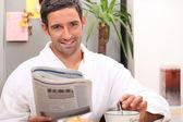 Man reading newspaper and having breakfast — Stock Photo