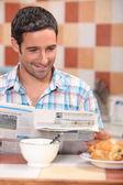 Homem lendo um jornal no café da manhã — Foto Stock