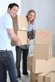 Couple stacking boxes — Stock Photo
