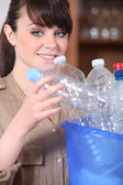 Young woman sorting plastic bottles — Stockfoto