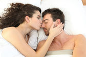Couple kissing in bed — Stock Photo
