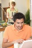 Man looking at his laptop while his wife prepares dinner — Stock Photo
