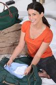 Young woman preparing travel bag — Stock Photo