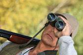 Hunter watching through binoculars — Stock Photo