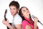 Young couple singing and playing guitar — Stock Photo