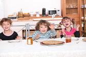 Three children gathered around breakfast table — Stock Photo