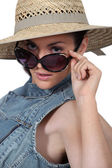 Woman wearing straw hat and sunglasses — Stock Photo