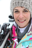 Woman resting skis on shoulder — Stock Photo