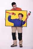 Full-length shot of artisan holding picture of blue collar with spanner — Stock Photo