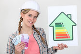 Woman holding cash and energy rating card — Stock Photo