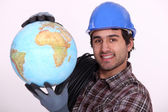 Manual worker holding globe — Stock Photo