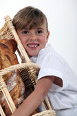 A little girl hugging a wickerwork bread bin full of bread — Stock Photo