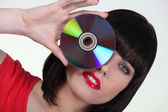Woman holding a cd to an her eye — Stock Photo