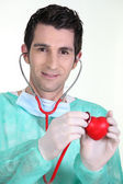 Doctor auscultating plastic heart — Stock Photo