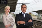 Una mujer rubia y un hombre maduro, bien vestido en una estación de tren — Foto de Stock