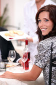Smiling woman at a dinner — Stock Photo