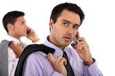 Two young businessmen talking on their cells — Stock Photo