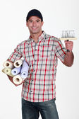 Portrait of do-it-yourselfer carrying wallpaper rolls and brush — Stock Photo