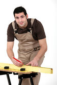 Carpenter measuring wood — Stock Photo