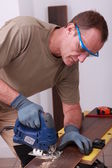 Handyman drilling a hole through a board — Zdjęcie stockowe