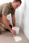 Man spreading tile adhesive on old tiles — Stock Photo