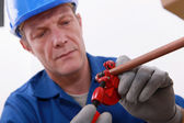 Plumber cutting a copper pipe with a pipe cutter — Stock Photo