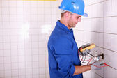 Electrician testing the current with a multimeter — Stock Photo