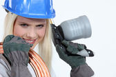 Blond woman with blowtorch and copper pipe — Stock Photo