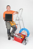 Builder with tools of the trade and a laptop computer — Stock Photo