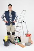 Proud tiler posing near ladder and tools — Stock Photo