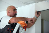Worker putting a doorway in a partition wall — Stock Photo