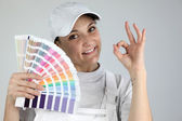 Painter giving the a-ok sign and holding a palette of colour samples — Stock Photo