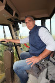 Farmer sitting in the cab of a combine harvester — Stock Photo