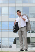 Businessman outside glass building holding satchel — Stock Photo