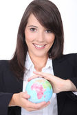 Portrait of a young brown-haired woman with a globe — Stock Photo