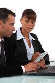 Mujer tomando notas como un hombre de negocios utiliza una computadora — Foto de Stock