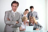 Confident male executive with his team of colleagues in the background — Stock Photo