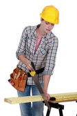 Woman sawing plank of wood — Stock Photo