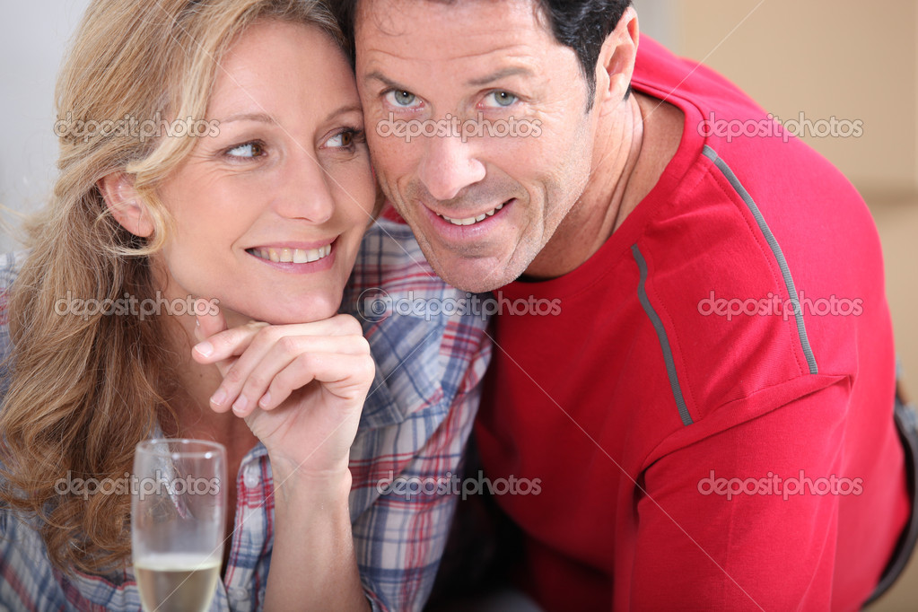 Blond woman holding champagne laid next to husband — Stock Photo #8101233
