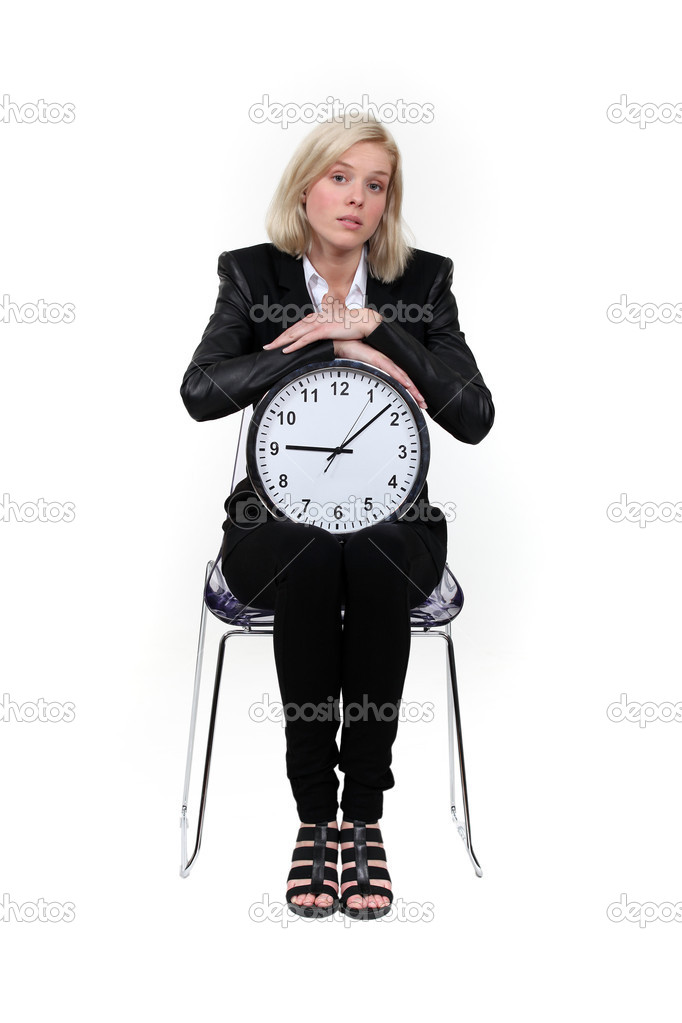 Woman sitting with a clock on her knees — Stock Photo #8102271