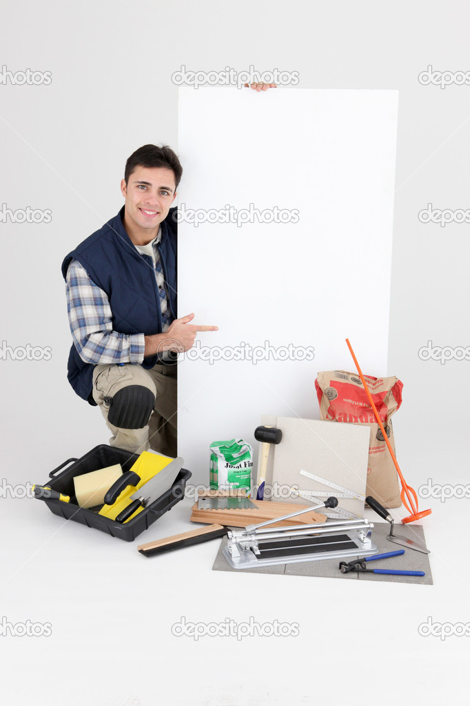 Laborer kneeling by supplies — Stock Photo #8107443