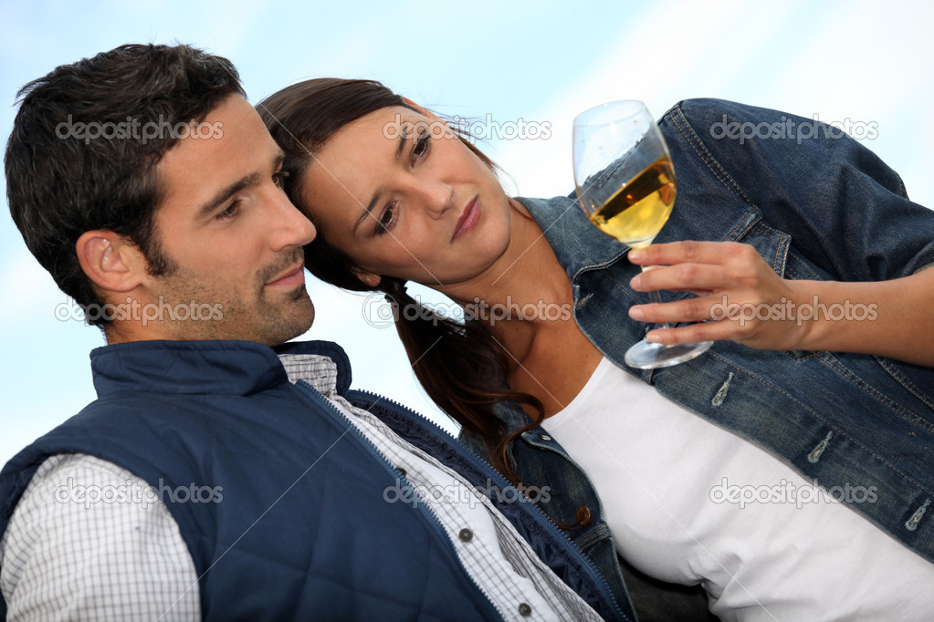 Couple looking at a glass of alcohol  Stock Photo #8107624