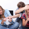 Three teenagers sat playing video games — Stock Photo #8110420